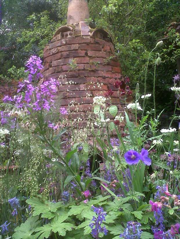 Chelsea Flower Show Artisan Garden - Mixed naturalistic plantings with reclaimed bridge chimney