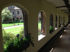 A view through the arches at Queens' College, Cambridge, with petunias spilling over the window sills