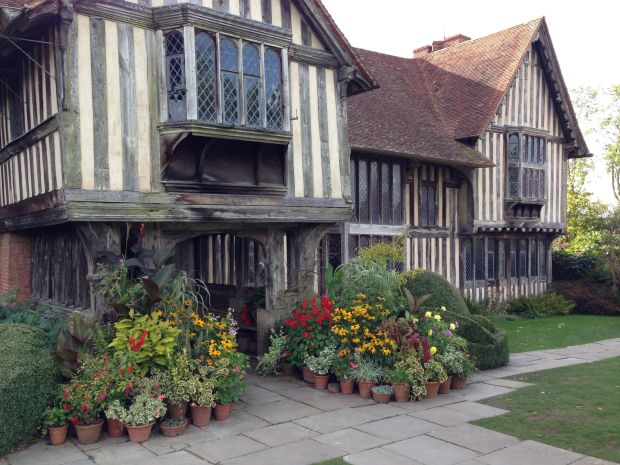 Massed, eclectic collection of potted plants at the front entrance to the Great Dixter house