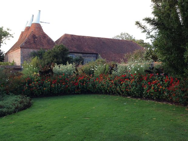 Hot orange and red perennial border near the entrance to Great Dixter