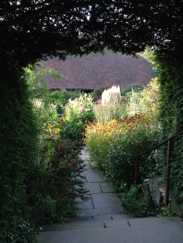 Looking through an archway to sun hitting the exuberant grasses and perennials