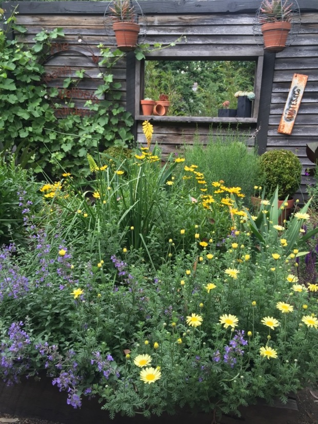 Abundant perennials give the air of a generous herbaceous border. The open 'window' provides views through to the fire pit area. Photo: Steven Wells