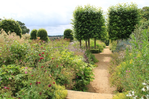 Soft, overflowing borders are broken up with pleached lime tree platforms at Broughton Grange