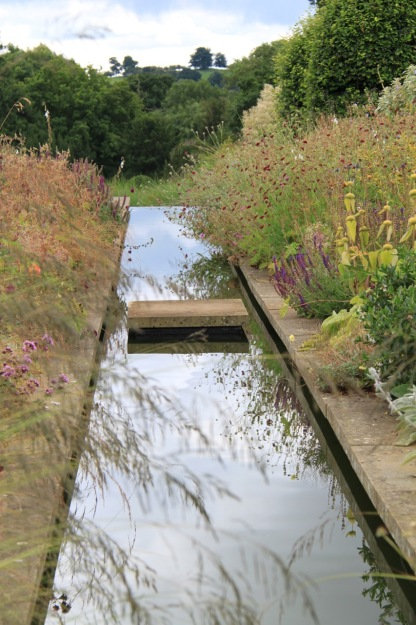 Wonderful reflections created by the still, still water at Broughton Grange, leading your eyes to the hills beyond