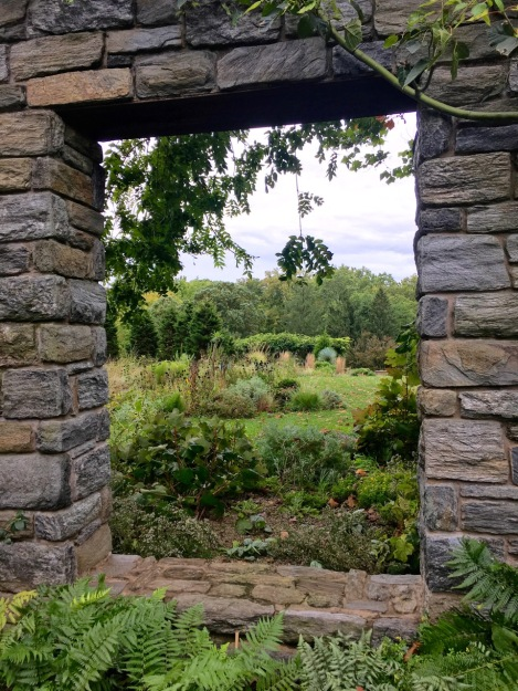 A view through a window in the Ruin Garden at Chanticleer Garden
